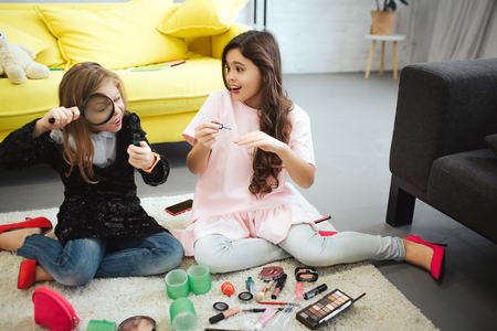 Photo pour Two teenagers sitting on carpet in room together. Girl on left look at bottle through loop. Her friend put some nail polish. They are busy. - image libre de droit