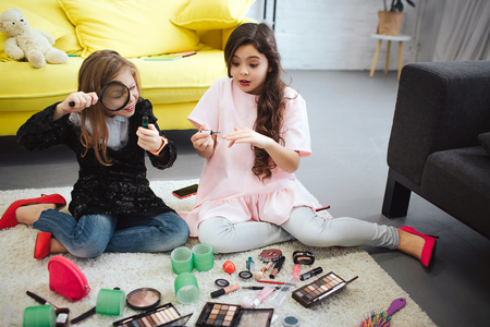 Foto de Two teenagers sitting on floor in room. Girl on left look at bottle through lenz. Teenager on right put some nail polish. She looks amazed. - Imagen libre de derechos