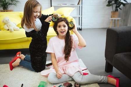 Foto de Amazed small girl look on camera. She suffer from pain. Her friend stand on knees and wrap hair on curler. She has fun. Girls wear clothes for adult women. - Imagen libre de derechos