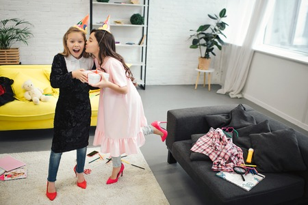 Foto de Happy small blonde girl hold present from her friend. Brunette kissing her in cheek. Teenagers wear clothes and shoes for adult women. They look happy in room. - Imagen libre de derechos
