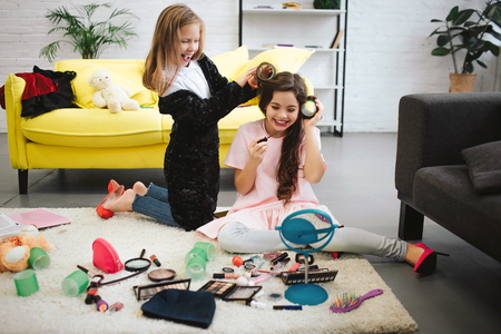 Photo pour Two happy teenage girls having fun in room. They sit and stand on carpet. Blonde girl curling her friends hair. Brunette doing makeup and look in mirror. She smiles. - image libre de droit
