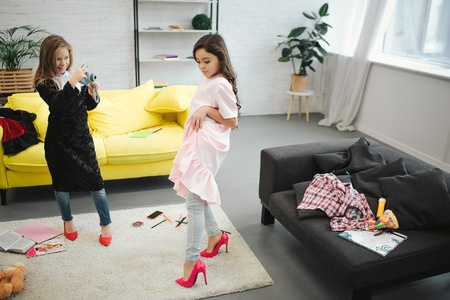 Foto de Small blonde girl taking picture of her friend on camera in room. Brunette posing and looking down. Both teenagers wear clothes and shoes for adult women. - Imagen libre de derechos