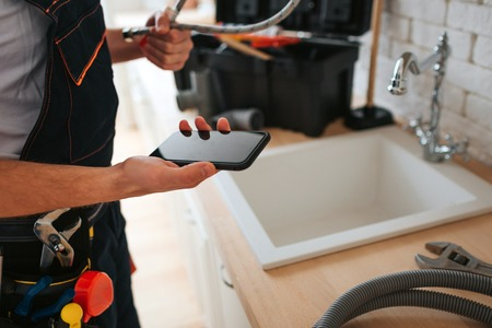 Photo pour Cut view of man standing in kitchen at sink. He hold phone and wrench. Hose on desk. - image libre de droit