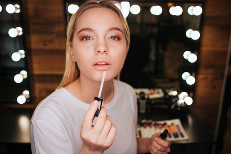 Foto de Young blonde woman applying lipgloss on lips. She look on camera. Serious and concentrated. Mirror with light bulbs behind. - Imagen libre de derechos