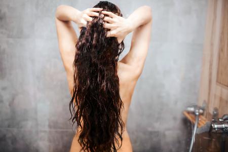 Foto de Young attractive sexy woman in shower. Dark-haired  model with well-built slim body stand and hold hair between hands. - Imagen libre de derechos