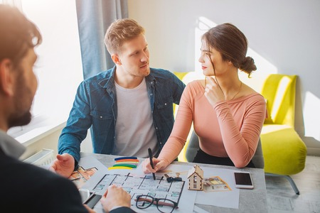 Foto de Couple buy or rent apartment together. They look at each other cheerful. Realtor sit in front of them. Bright sunlight comes out of window. - Imagen libre de derechos