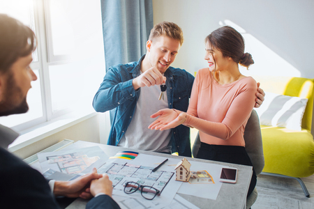 Foto de Couple buy or rent apartment together. Happy young woman get keys from man. Realtor sit in front of them. Apartment plan and phone on table. - Imagen libre de derechos