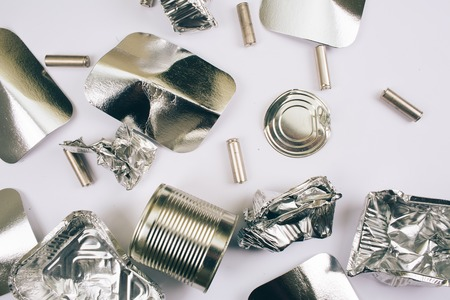 Photo for Plastic pollution concept. Foil containers, silver cardboards, metal cans and batteries on white background, top view. Single-use plastic. New rules to reduce plastic waste, EU directive. Be plastic free - Royalty Free Image
