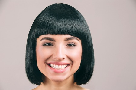Photo for Young woman with black hair posing on camera. Cheerful nice model smile. Black bob haircut. Isolated on light background. - Royalty Free Image
