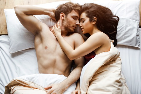 Foto de Young sexy couple have intimacy on bed. Lying together very close. Female model embrace guy. Lying with closed eyes. Sex in bed. White pillows. Sleeping. - Imagen libre de derechos