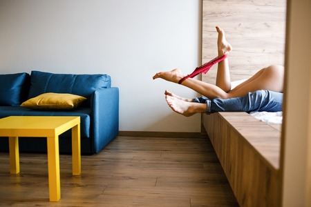 Foto de Young sexy couple have intimacy on bed. Cut view of womans underwear between legs posing on camera. Model lying on man. - Imagen libre de derechos