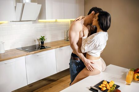 Foto de Young sexy couple have intimacy in kitchen in night. Shirtless well-built guy lean to woman and kiss her. Hot sensual model touch man and sit on table. Wear white shirt and lingerie. - Imagen libre de derechos