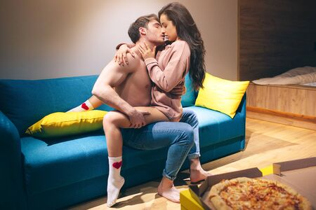 Photo pour Young couple have intimacy in kitchen in night. Passionate shirtless man hold woman on his legs and kissing her. Seductive sensual model in sex position enjoying. Pizza on table. - image libre de droit