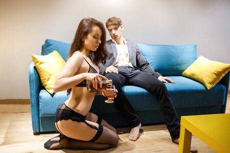 Foto de Young sexy couple having intimacy in living room. Man in jacket sit on sofa and look how woman pour alcohol in glass. Beauty in black lingerie sit on floor. Master and slave. Lust and passion. - Imagen libre de derechos