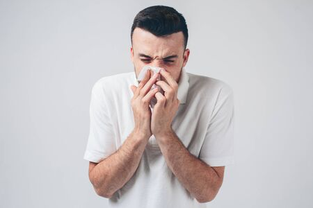 Photo pour Young man isolated over background. Sick person with nose running. Using white napkin. Coronavirus danger. Ill male person inside studio room. - image libre de droit