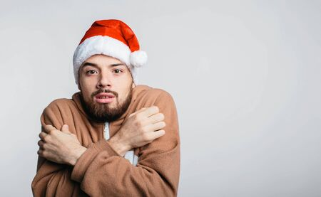 portrait of man dressed in pajamas i Christmas red hat in cold isolated