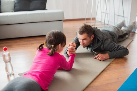 Foto de father and daughter are training at home. Workout in the apartment. Sports at home. Compete in arm wrestling and lie on a yoga mat - Imagen libre de derechos