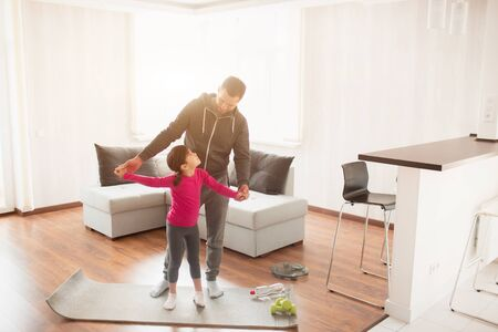 Photo pour father and daughter are training at home. Workout in the apartment. Sports at home. They are standing on a yoga mat. - image libre de droit