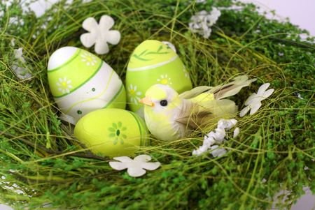 green nest with toy bird and eastereggs