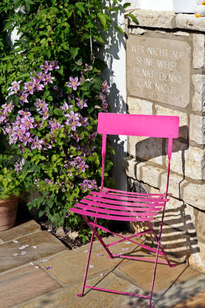 pink folding chair on the terrace, behind it an aphorism on a marble top