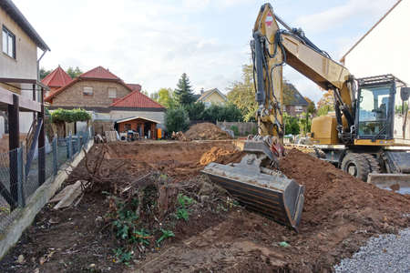 Photo for Excavator in front of an excavation pit to build a house - Royalty Free Image