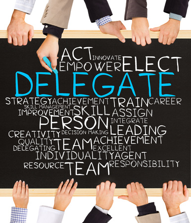 Photo of business hands holding blackboard and writing DELEGATE word cloud