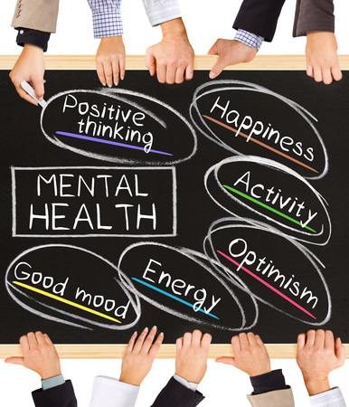Foto de Photo of business hands holding blackboard and writing MENTAL HEALTH diagram - Imagen libre de derechos