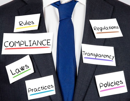 Photo of business suit and tie with COMPLIANCE concept paper cards