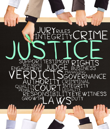 Photo of business hands holding blackboard and writing JUSTICE concept