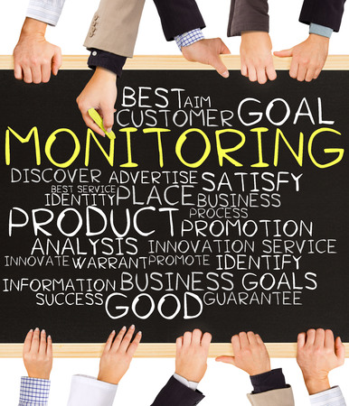 Photo of business hands holding blackboard and writing MONITORING concept