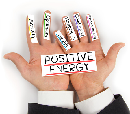 Photo of hands holding POSITIVE ENERGY paper cards with concept words