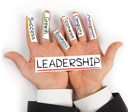 Photo of hands holding LEADERSHIP paper cards with concept words