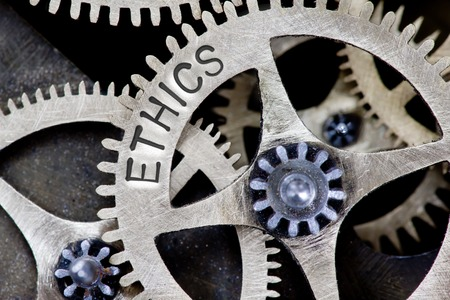Macro photo of tooth wheel mechanism with ETHICS concept words
