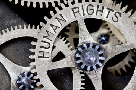 Macro photo of tooth wheel mechanism with HUMAN RIGHTS concept words