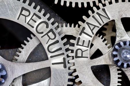 Foto de Macro photo of tooth wheel mechanism with imprinted RECRUIT, RETAIN concept words - Imagen libre de derechos