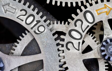Photo pour Photo of tooth wheel mechanism with numbers 2020, 2019 imprinted on metal surface. New Year concept. - image libre de droit