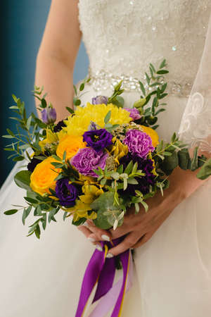 Foto de Bridal bouquet on the wedding day. A lovely girl holds a bouquet of yellow roses and purple flowers. - Imagen libre de derechos