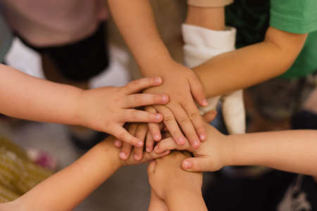 Photo pour Children's hands piled on top of each other. Children's team and team building among the little guys. - image libre de droit