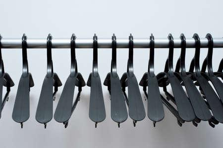 Photo pour black plastic hangers hang on a light background. many different hangers. floor coat rack. - image libre de droit