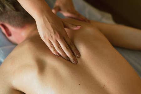 Photo pour Woman massages under the shoulder blade on the back. Masseur does massage to a man lying on a couch - image libre de droit