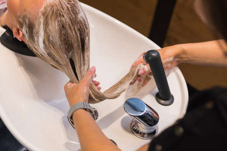 Foto für washing your hair in the cabin. a hairdresser washes hair with a shampoo to a blonde girl - Lizenzfreies Bild