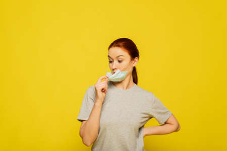 Photo pour Portrait of young anxious woman in panic in facial protective mask, close up, copy space, isolated on yellow background. Coronavirus, flu, covid-19, dust allergy, protection against virus. - image libre de droit