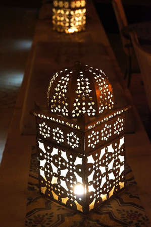Close up view of an illuminated and metallic lantern from arab tradition