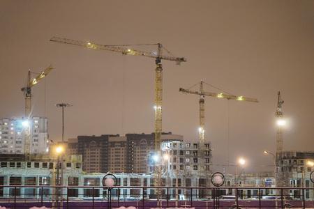 Photo pour construction cranes on the construction site at night - image libre de droit