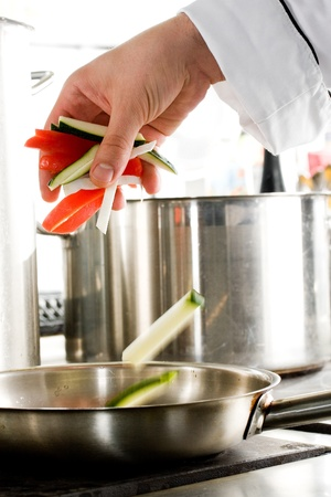 Chef hands add vegetables on a frying pan on professional kitchen