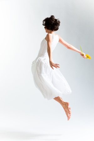 Young woman in with dress flying with flower