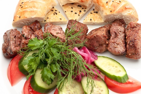 Close-up of beef barbecue colorfully decorated with vegetables and bread