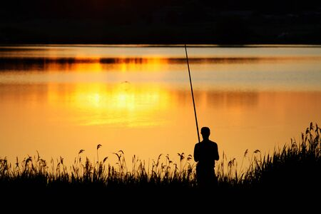Photo pour Man fishing at sunset. Backlit silhouette of a fisherman - image libre de droit
