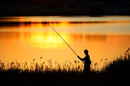 Photo pour Fisherman fishing at dusk with a rod. Backlit silhouette of a fisherman - image libre de droit