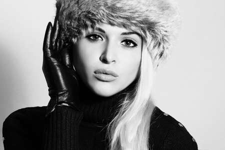 Monochrome portrait of Young Woman in Fur Hat. Beautiful Blond Girl in Black Leather Gloves. Winter Fashion Beauty